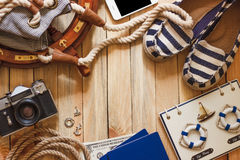 Striped slippers, camera, phone and maritime decorations, wooden background Stock Images