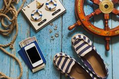 Striped slippers, phone and maritime decorations on the wooden background Royalty Free Stock Photography