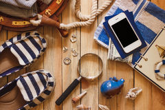 Striped slippers, towel, piggy bank, phone and maritime decorations Royalty Free Stock Photo