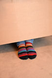 Striped socks. Looking out under a paper box Stock Images