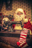 Striped socks. Santa Claus is sewing on a sewing machine striped socks for Christmas royalty free stock images