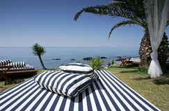 Striped Sunlounger and sunny sea views. Striped Luxury Sunlounger with palm trees and sunny sea views stock photo