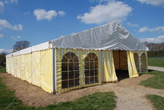 Striped tent, England. A yellow and white striped tent standing in a field in Kent, England Stock Images