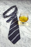 Striped tie with a glass of brandy on the marble table Royalty Free Stock Image