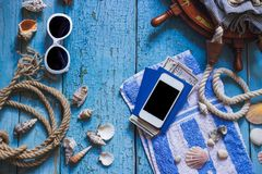 Striped towel, phone and maritime decorations on the wooden background Royalty Free Stock Photos