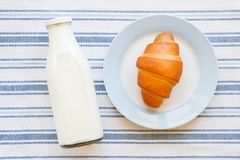 On a striped towel there is a glass bottle with fresh milk and freshly baked bakery products, croissants on a plate. The concept royalty free stock images