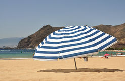 Striped umbrella on the beach Royalty Free Stock Photos