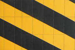 Striped Wall. Cement wall painted with yellow and black strips royalty free stock images