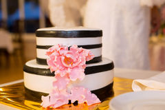 Striped wedding cake and pink flower royalty free stock photos