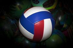 Striped volleyball ball against painted green balls stock image