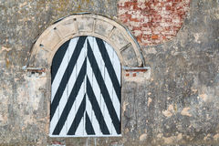 Striped window on brick facade. Striped window on a brick facade of the old fort Stock Photo