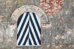 Striped window on brick facade Stock Photo