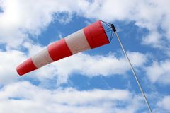 Striped windsock at airport on the background of beautiful clouds.  stock image