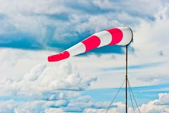Striped windsock at airport on the background of beautiful clouds Royalty Free Stock Image