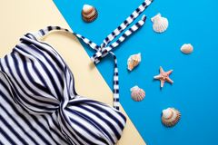 Striped women`s swimsuit and sea shells on blue and yellow background. Flat lay composition, concept of summer holidays, vacation. Sea resort, rest on sea royalty free stock images