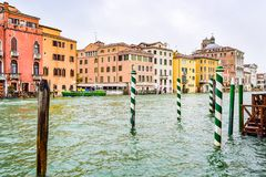 Striped and wooden mooring poles along sides of Grand Canal in Venice, Italy. stock photo
