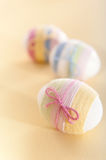 Striped yarn wrapped Easter eggs Royalty Free Stock Images