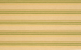 Stripes Background. A set of repeated yellow and green stripes sit on a piece of fabric Royalty Free Stock Photo