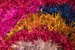 Stripes of colored tinsel. Rows of multicolored, shiny tinsel. Preparation for a party, carnival, holiday attribute. Macro photography, artificial lighting Stock Image