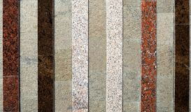 Stripes of different types and colors of marble on gray granite background royalty free stock images