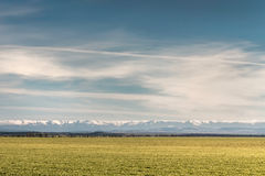 Stripes - grass on a background of snow-capped mountains and sky Stock Photo