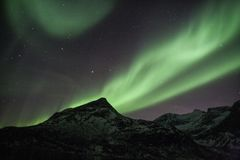 Stripes of northern Lights behind the mountains in Tromso royalty free stock images