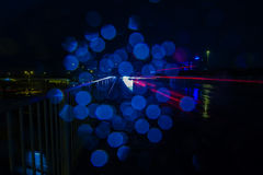 Stripes of red light and blue reflections. From car`s driving by on a wet bridge royalty free stock images