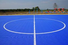 Stripes  soccer field on blue floor background. Royalty Free Stock Photos