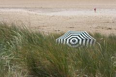 Stripey在象草的沙丘的沙滩伞 免版税库存图片