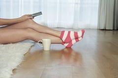Stripey袜子的妇女与遥控 免版税库存照片