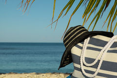 Stripey beach bag and hat. Under palm frond Royalty Free Stock Images