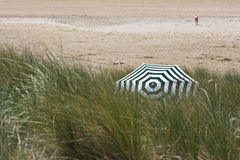 Privacy: Striped beach umbrella in grassy dunes Royalty Free Stock Images