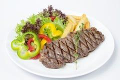 Striploin牛排服务用新鲜的油煎的沙拉和法语 免版税库存照片