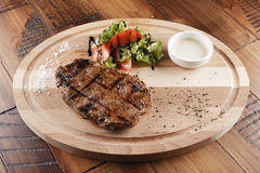 Striploin beef steak. With sauce on wooden surface. wooden background Royalty Free Stock Photography