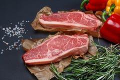 Striploin biff med söt peppar, saltar och rosmarinbakgrund Arkivfoto