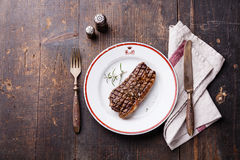 Striploin steak on plate and fork and knife Royalty Free Stock Photography