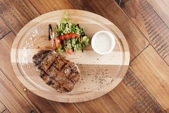 Striploin steak. With sauce on wooden surface. wooden background Royalty Free Stock Photo
