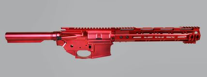 Stripped AR15 Upper, Lower, buffer tube and handguard painted with a bright red coating. Stripped AR15 receiver set, buffer tube and handguard painted with stock photo