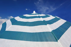 Stripped beach parasol at blue sky Royalty Free Stock Photos