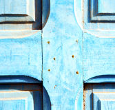 stripped paint in the blue wood door and rusty nail Royalty Free Stock Images