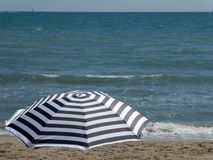 Stripped Umbrella on the Beach royalty free stock image
