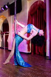 Stripper girl pole dancing in costume Royalty Free Stock Image
