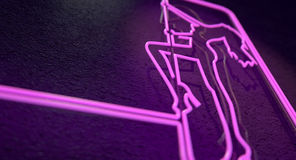 Stripper Sign. An illuminated neon pink sign for a strip club mounted on a wall incorporating a dancing girl stock photo
