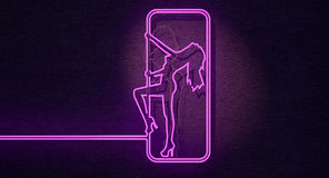 Stripper Sign. An illuminated neon pink sign for a strip club mounted on a wall incorporating a dancing girl royalty free stock photography