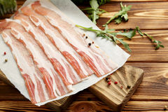Strips of bacon. Crispy strips of bacon on a brown wooden background Royalty Free Stock Photo