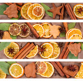 Strips are composed of dried oranges, anise star, cinnamon sticks and gingerbread on a brown background Stock Image