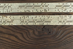 Strips of old punched tape on a dark wooden surface Royalty Free Stock Photography