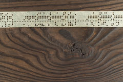 Strips of old punched tape on a dark wooden surface Stock Photos