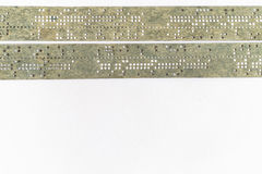 Strips of old punched tape on a white surface Royalty Free Stock Photos