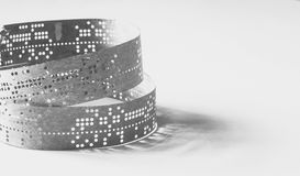 Strips of old punched tape on a white surface Stock Image